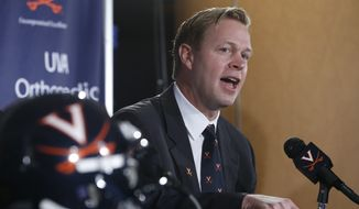 New University of Virginia NCAA college head football coach, Bronco Mendenhall, gestures during a news conference at the school  in Charlottesville, Va., Monday, Dec. 7, 2015.  Mendenhall takes over after his current team Brigham Young University competes in it's bowl game. (AP Photo/Steve Helber)