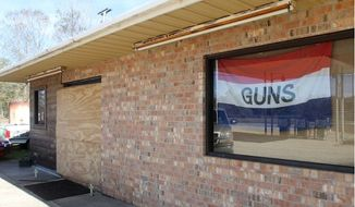 The front door of the McLemore gun shop, north of Picayune, Miss. was boarded up Sunday, Jan. 24 after the owner and his son were killed in a shootout with two customers. (Image: Sun Herald)