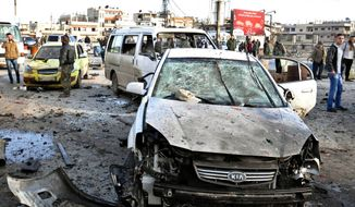 In this photo released by the Syrian official news agency SANA, Syrian citizens gather at the scene where twin bombs exploded at a government-run security checkpoint, at the neighborhood of Zahraa, in Homs province, Syria, Tuesday, Jan. 26, 2016. (SANA via AP)