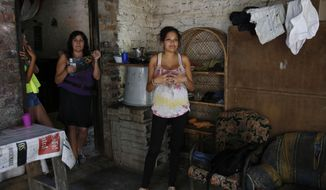 Kerly Ariza, 17 and 20-weeks-pregnant, right, stands at her home in Ibague, Colombia, Tuesday, Jan. 26, 2016. Ariza was diagnosed with clinical symptoms of the Zika virus at a local hospital and is awaiting for the results of laboratory tests. Minister of Health Alejandro Gaviria said that at least 16.000 people have already been already infected with the Zika virus in Colombia, among them more than 500 pregnant women. (AP Photo/Fernando Vergara)