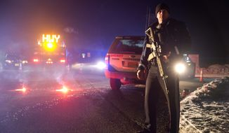 Sgt. Tom Hutchison stands in front of an Oregon State Police roadblock on Highway 395 on Tuesday, Jan. 26, 2016 between John Day and Burns, Ore. The FBI on Tuesday arrested the leaders of an armed group that has occupied a federal wildlife refuge in eastern Oregon for the past three weeks. (Dave Killen/The Oregonian via AP)