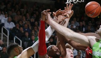 FILe - In this Jan. 23, 2016, file photo, Michigan State's Denzel Valentine (45), Maryland's Rasheed Sulaimon (0) and Jake Layman, rear, and Michigan State's Matt Costello, right, vie for a rebound during the second half of an NCAA college basketball game in East Lansing, Mich. No. 8 Maryland will be looking to rebound Thursday night, Jan. 28 against No. 3 Iowa in more ways than one. The Terrapins are coming off a loss to Michigan State and have yielded 33 offensive rebounds in their last two games. (AP Photo/Al Goldis, File)