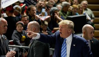 Republican presidential candidate Donald Trump points to members of the audience as he departs after speaking at a rally at Muscatine High School in Muscatine, Iowa, Sunday, Jan. 24, 2016. (AP Photo/Andrew Harnik)
