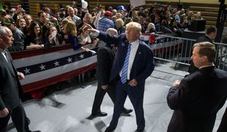 Republican presidential candidate Donald Trump waves to members of the audience as he departs after speaking at a rally at Muscatine High School in Muscatine, Iowa, Sunday, Jan. 24, 2016. (AP Photo/Andrew Harnik)