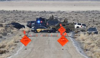 Law enforcement personnel block an access road to the Malheur National Wildlife Refuge, Wednesday, Jan. 27, 2016, near Burns, Ore. Authorities were restricting access on Wednesday to the Oregon refuge being occupied by an armed group after one of the occupiers was killed during a traffic stop and eight more, including the group's leader Ammon Bundy, were arrested. (Thomas Boyd/The Oregonian via AP) MAGS OUT; TV OUT; NO LOCAL INTERNET; THE MERCURY OUT; WILLAMETTE WEEK OUT; PAMPLIN MEDIA GROUP OUT; MANDATORY CREDIT