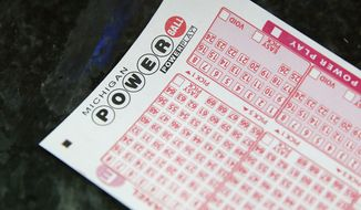 A Powerball ticket is shown at Coach Liquor in Detroit. (Associated Press)