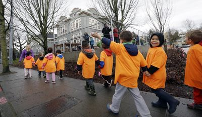 A preschooler waves to a teacher ahead as his class returns after a walk to their school housed in a community building in Seattle's University District, Wednesday, Jan. 27, 2016. Across the country, just 14 percent of neighborhoods manage to be at once affordably priced, walkable and near decent schools. And many of those neighborhoods exist in only two cities: Washington and Seattle, according to a new analysis released Wednesday by the real estate brokerage Redfin. (AP Photo/Elaine Thompson)