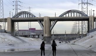 People photograph the 6th Street Bridge that spans the Los Angeles River, Wednesday, Jan. 27, 2016, in Los Angeles, before it is closed permanently for demolition. The landmark bridge, dating to the 1930s, is being replaced due to deterioration caused by a chemical reaction in the concrete. The $449 million project to build a replacement bridge, designed by architect Michael Maltzan, is expected to be completed by 2019 at the earliest. (AP Photo/Damian Dovarganes)