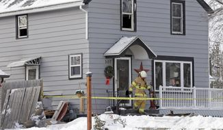 Sheboygan Falls Assistant Fire Chief Wade Ubbelohde leaves a home on the 500 block of Western Avenue in Sheboygan Falls, Wis., Wednesday, Jan. 27, 2016, the day after a fatal fire. Three children, including an 11-year-old who tried to rescue two younger children from the fire, died officials said. A fourth child, a 9-year-old girl, escaped from the burning home. (Mike De Sisti/Milwaukee Journal-Sentinel via AP)