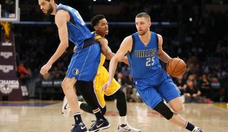 Dallas Mavericks' Chandler Parsons, right, drives past Los Angeles Lakers' Anthony Brown, center, while Mavericks' Salah Mejri, left, sets a pick during the first half of an NBA basketball game, Tuesday, Jan. 26, 2016, in Los Angeles. (AP Photo/Danny Moloshok)