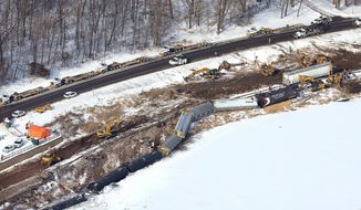 In this aerial photo, crews work the scene of a train derailment Wednesday, Jan. 27, 2016, along Hwy. 26 south of Brownsville, Minn. Authorities say two of six derailed train cars have broken through the ice on the Mississippi River in southeastern Minnesota. (Erik Daily/La Crosse Tribune via AP) MANDATORY CREDIT