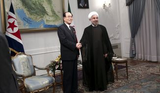 Iranian President Hasan Rouhani (right) shakes hands with Kim Yong Nam, a top North Korean leader, at the start of a meeting in Tehran on Aug. 3, 2013. (Associated Press) **FILE**
