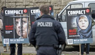 A policeman stands in front of protesters  holding posters  depicting German Chancellor Angela Merkel  with headscarf , and behind bars,  prior to a visit of the chancellor to  the official opening of the Fraunhofer Institute for Microstructure of Materials and Systems IMW in Halle, central Germany, Monday, Jan. 25, 2016. (AP Photo/Jens Meyer) ** FILE **