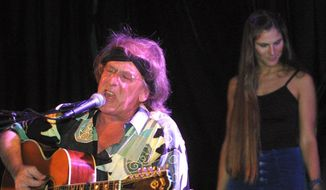 "This June 20, 2001, file photo shows Jefferson Starships' Paul Kantner, left, performing in front of Diana Mangano during the ""Freedom Sings"" benefit concert in New York.  Kantner, an original member of the seminal 1960s rock band Jefferson Airplane and the eventual leader of successor group Jefferson Starship, has died at age 74. (AP Photo/Shawn Baldwin, File)"