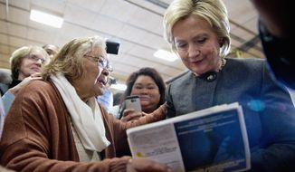 In this photo taken Jan. 25, 2016, Democratic presidential candidate Hillary Clinton signs an autograph for a supporter during a campaign event at the Knoxville School District Administration Office in Knoxville, Iowa. (AP Photo/Mary Altaffer)