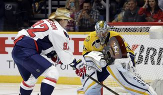 Nashville Predators goalie Pekka Rinne (35) uses a guitar instead of a stick as Washington Capitals center Evgeny Kuznetsov (92) shoots during the breakaway challenge at the NHL hockey All-Star game skills competition Saturday, Jan. 30, 2016, in Nashville, Tenn. (AP Photo/Mark Humphrey)