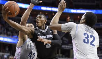 Providence guard Kris Dunn, center, goes to the basket against Georgetown center Bradley Hayes (42) and guard Kaleb Johnson (32 ) during the first half of an NCAA college basketball game Saturday, Jan. 30, 2016, in Washington. (AP Photo/Nick Wass)