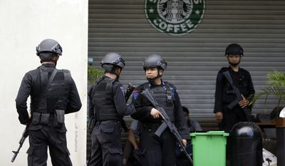 Indonesian police officers guard a Starbucks cafe in Jakarta, Indonesia, on Jan. 16, two days after it was a target of a suicide bombing attack funded by the Islamic State. (Associated Press)