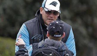 Carolina Panthers head coach Ron Rivera signs an autograph before practice for the NFL football team in Charlotte, N.C., Thursday, Jan. 28, 2016. (AP Photo/Chuck Burton)