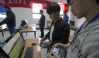In this Oct. 17, 2015 photo, students learn to operate drones at a school run by TT Aviation Technology in Beijing. TT Aviation Technology Co. - and their instructors - are part of a new cottage industry sprouting up in China, where drones are being deployed in rising numbers and touted as a game-changer in agriculture, logistics, film production and law enforcement. (AP Photo/Ng Han Guan)