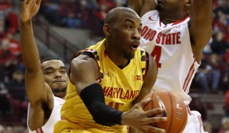 Maryland's Rasheed Sulaimon, center, passes the ball between Ohio State's Keita Bates-Diop, left, and Daniel Giddens during the first half of an NCAA college basketball game in Columbus, Ohio, Sunday, Jan. 31, 2016. (AP Photo/Paul Vernon)