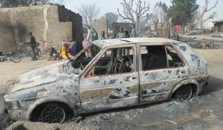 Children gather around a burnt out car following an attack by Boko Haram in Dalori village 5 kilometers (3 miles) from Maiduguri, Nigeria , Sunday Jan. 31, 2016. (AP Photo/Jossy Ola)