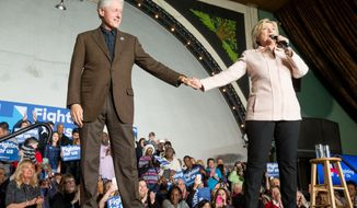 Democratic presidential candidate Hillary Clinton holds hands with her husband former President Bill Clinton as she takes the stage to speak at a rally at the Col Ballroom in Davenport, Iowa, Friday, Jan. 29, 2016. (AP Photo/Andrew Harnik)