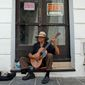 A man plays his guitar while he begs for money in front of a closed down business in Old San Juan, Puerto Rico, on June 29, 2015. (Associated Press) **FILE**