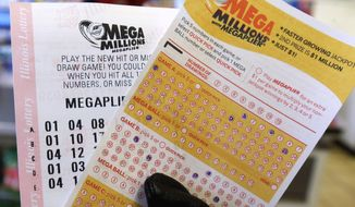 A customer holds a Mega Millions ticket at a convenience store in Chicago. (Associated Press)