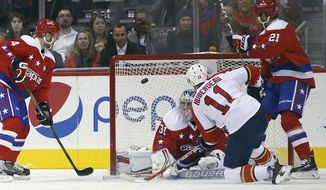 Florida Panthers center Jonathan Huberdeau (11) scores a goal past Washington Capitals goalie Philipp Grubauer (31), from Germany, with Capitals center Brooks Laich (21) nearby, during the first period of an NHL hockey game, Tuesday, Feb. 2, 2016, in Washington. (AP Photo/Alex Brandon)