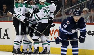 Dallas Stars celebrate a goal by John Klingberg (3) as Winnipeg Jets' Bryan Little (18) skates past during the second period of an NHL hockey game Tuesday, Feb. 2, 2016, in Winnipeg, Manitoba. (Trevor Hagan/The Canadian Press via AP)