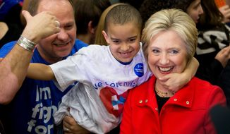 Democratic presidential candidate Hillary Clinton is embraced by a young member of the audience at a recent rally. (Associated Press/File)