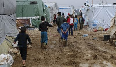 Syrian refugee children walk in mud from the heavy rain at a refugee camp in the town of Hosh Hareem, in the Bekaa valley, east Lebanon, in this Jan. 4, 2016, file photo. (AP Photo/Hassan Ammar, File)