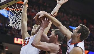 Boston College center Dennis Clifford, center, is swarmed by Virginia center Jack Salt (33) and forward Evan Nolte, right, during the first half of an NCAA college basketball game in Charlottesville, Va., Wednesday, Feb. 3, 2016. (AP Photo/Steve Helber)