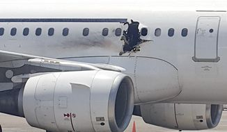 In this Tuesday, Feb. 2, 2016, photo, a hole is photographed in a plane operated by Daallo Airlines as it sits on the runway of the airport in Mogadishu, Somalia. A gaping hole in the commercial airliner forced it to make an emergency landing at Mogadishu's international airport late Tuesday, officials and witnesses said. (AP Photo)