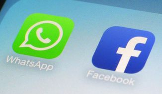 This Feb. 19, 2014, file photo, shows WhatsApp and Facebook app icons on a smartphone in New York. WhatsApp, the Internet messaging service owned by Facebook, announced in February 2016 that it now has 1 billion users worldwide. (AP Photo/Patrick Sison, File)