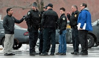 Police talk as they investigate the scene of gunfire with a suspect of a fatal shooting of a woman, at a shopping area in Madison, Wis., Wednesday, Feb. 3, 2016. Madison police said the suspect is in custody in the fatal shooting in a grocery store parking lot. At center is Madison Police Chief Mike Koval. (Michael P. King/Wisconsin State Journal via AP) MANDATORY CREDIT