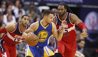 Golden State Warriors guard Stephen Curry (30) moves away from Washington Wizards guard Garrett Temple (17) and center Nene (42), from Brazil, during the first half of an NBA basketball game Wednesday, Feb. 3, 2016, in Washington. (AP Photo/Alex Brandon)