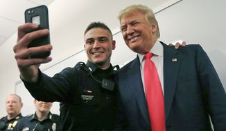 Patrolman James Pittman poses for a selfie with Republican presidential candidate Donald Trump. Mr. Trump was on the trail Thursday glad-handing in in New Hampshire, where he holds a sizable lead despite coming in second in Iowa. (Associated Press)
