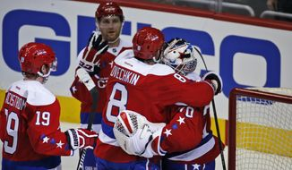 Washington Capitals left wing Alex Ovechkin (8), from Russia, reacts with Washington Capitals goalie Braden Holtby (70) after an NHL hockey game against the New York Islanders, Thursday, Feb. 4, 2016, in Washington. The Capitals won 3-2. (AP Photo/Alex Brandon)