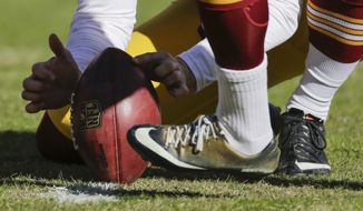 Washington Redskins punter Tress Way (5) hols the ball for Washington Redskins kicker Dustin Hopkins (3) as they warm up before an NFL football game against the Buffalo Bills in Landover, Md., Sunday, Dec. 20, 2015. (AP Photo/Mark Tenally)