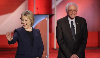 Hillary Clinton and and Sen. Bernard Sanders greet the audience before the Democratic debate Thursday in Durham, N.H. (Associated Press)
