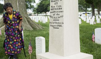 "ADVANCE FOR USE SATURDAY, FEB. 6, AND THEREAFTER - FILE - In this May 26, 2014, file photo, Edwina W. Lindsey, a member of the St. Louis African-American History and Genealogy Society, looks at a graveside marker at Jefferson Barracks National Cemetery in St. Louis. Graves of black soldiers who served in the Civil War are sometimes marked ""U.S.C.I."" for United States Colored Infantry, and it's been 150 years since those units began returning home from their service in the South, where more than 175,000 members fought - and in some cases, died - to free fellow African-Americans from slavery. (AP Photo/Whitney Curtis, File)"