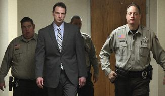 FILE - In this Jan. 25, 2016 file photo, Curtis Lovelace, second from left, is escorted to a courtroom for the start of his murder trial by sheriff's deputies at the Adams County Courthouse in Quincy, Ill.  Lovelace, a former University of Illinois football star and Adams County prosecutor, is accused of suffocating his wife, Cory, on Feb. 14, 2006.  Closing arguments are set to begin Thursday, Feb. 4, 2016. (Phil Carlson/The Quincy Herald-Whig via AP, File)  MANDATORY CREDIT
