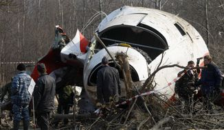 """FILE - In this April 14, 2010 file photo emergency ministry workers preparing to load the wreckage of the Polish presidential plane on a  transporter just outside the Smolensk airport, western Russia, Poland's government has opened a new investigation into the 2010 plane crash in Russia that killed President Lech Kaczynski, the twin brother of the chairman of the country's ruling right-wing party. Defense Minister Antoni Macierewicz announced the new investigation Thursday Feb. 4, 2016  in Warsaw, saying the original investigation by Polish authorities was riddled with """"mistakes"""" and """"abnormalities.""""  (AP Photo/Mikhail Metzel)"""