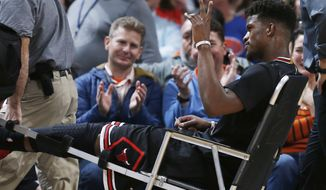 Chicago Bulls guard Jimmy Butler waves to fans as they applaud him while Butler is taken off the court after being injured late in the first half of his team's NBA basketball game against the Denver Nuggets on Friday, Feb. 5, 2016, in Denver. (AP Photo/David Zalubowski)
