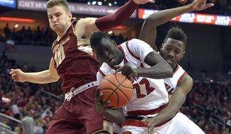 Louisville's Deng Adel (22) and Chinanu Onuaku, right, battle Boston College's Ervins Meznieks (10) for a rebound during the first half of an NCAA college basketball game, Saturday, Feb. 6, 2016, in Louisville Ky. (AP Photo/Timothy D. Easley)