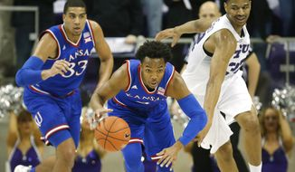 Kansas guard Devonte' Graham, center, steals the ball from TCU forward Karviar Shepherd, right, as Kansas forward Landen Lucas (33) looks on during the first half of an NCAA college basketball game, Saturday, Feb. 6, 2016, in Fort Worth, Texas. (AP Photo/Ron Jenkins)
