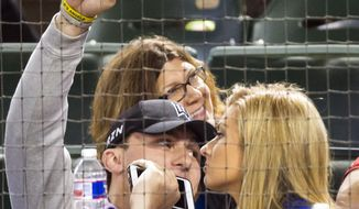 FILE - In this Tuesday, April 14, 2015 file photo, Johnny Manziel waves to the crowd as he watches from the seats behind home plate with Colleen Crowley as the Texas Rangers face the Los Angeles Angels in a baseball game at Globe Life Park in Arlington, Texas. (Smiley N. Pool/The Dallas Morning News) MANDATORY CREDIT; MAGS OUT; TV OUT; INTERNET USE BY AP MEMBERS ONLY; NO SALES