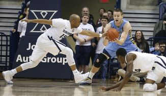 Marquette center Luke Fischer, center, grabs a loose ball in front of Xavier guard Myles Davis (15) and Edmond Sumner, right, during the first half of an NCAA college basketball game Saturday, Feb. 6, 2016, in Cincinnati. (AP Photo/Gary Landers)